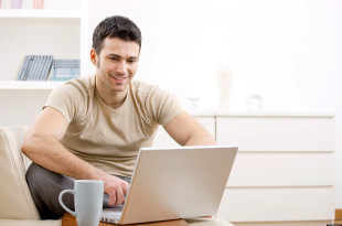 Happy young man in t-shirt sitting on sofa at home, working on laptop computer, smiling.; Shutterstock ID 29143153; PO: The Huffington Post; Job: The Huffington Post; Client: The Huffington Post; Other: The Huffington Post